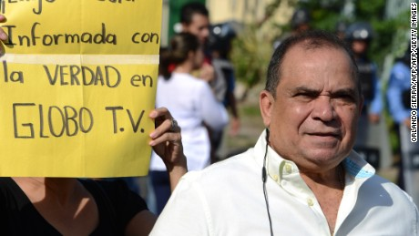 "The director of Globo TV, Honduran journalist David Romero, protests for the closure of the opposition channel, next to a sign reading ""Conatel, I demand to be informed with the truth in Globo TV"", outside the National Telecommunications Commission (CONATEL) headquarters in Tegucigalpa on May 23, 2016. Protesters accused the government of taking reprisals for the corruption denunciations the channel has done. / AFP / ORLANDO SIERRA        (Photo credit should read ORLANDO SIERRA/AFP/Getty Images)"