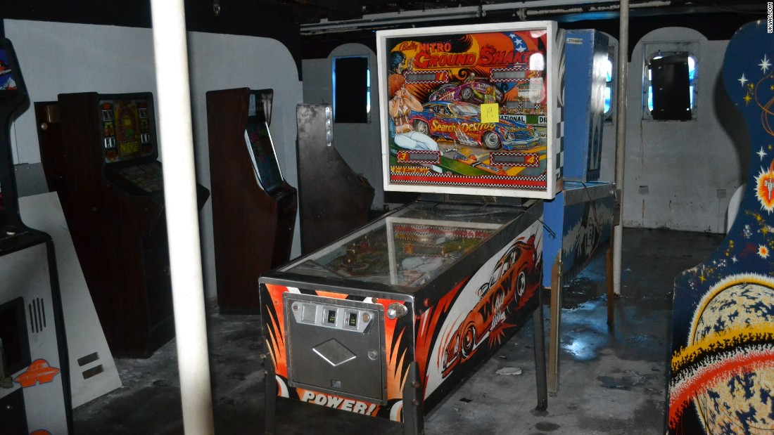 """Wow"" ""Power!"" Just two of the exclamations which adorn the Ground Shaker pinball machine. The machine sits back to back with a blue pinball machine in a room that is stripped bare of any previous decoration."