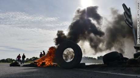 Union members stand next to tires set ablaze near an oil refinery this week in Donges.