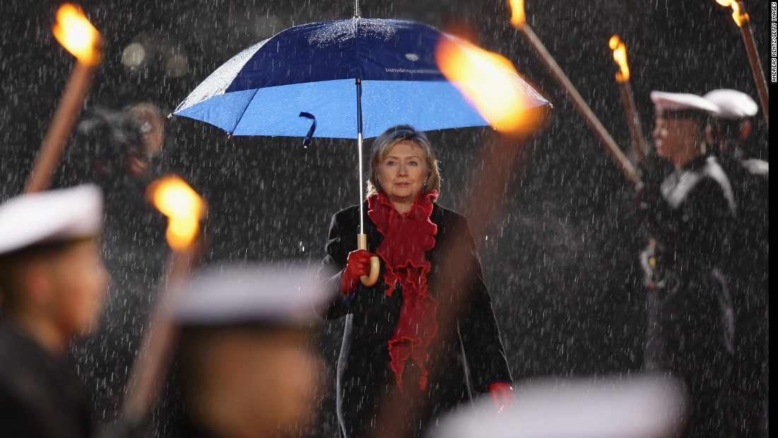 Clinton reviews an honor guard carrying torches at Bellevue Castle on November 9, 2009, in Berlin.