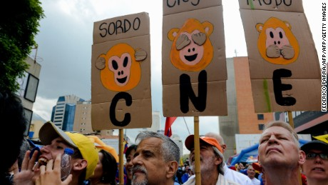 "Opponents to the government of Venezuelan President Nicolas Maduro hold signs reading ""CNE deaf, blind, mute"" -referring to the National Electoral Council (CNE) as they take part in a demonstration in Caracas on May 14, 2016.   Venezuela braced for protests Saturday after Maduro declared a state of emergency to combat the ""foreign aggression"" he blamed for an economic crisis that has pushed the country to the brink of collapse. / AFP / FEDERICO PARRA        (Photo credit should read FEDERICO PARRA/AFP/Getty Images)"