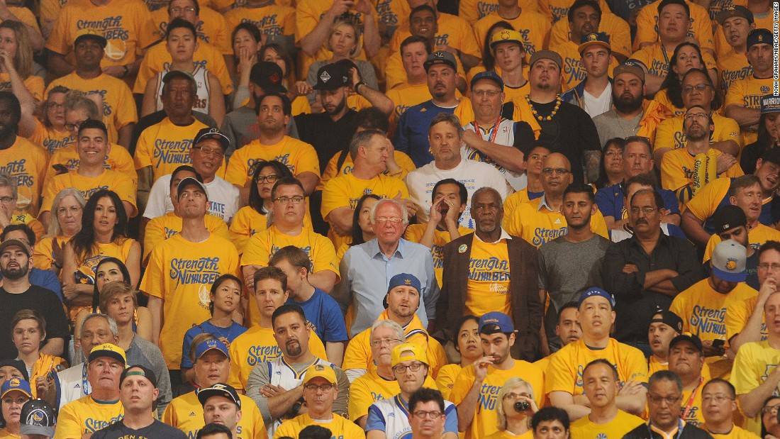 U.S. Sen. Bernie Sanders, at center in the light-blue shirt, watches a playoff basketball game in Oakland, California, on Monday, May 30. The presidential candidate, campaigning for the state's upcoming primary, saw the Golden State Warriors win Game 7 of the NBA's Western Conference Finals.