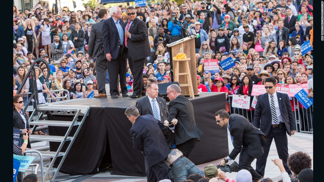 "A protester <a href=""http://www.cnn.com/2016/05/30/politics/secret-service-bernie-sander-protesters/"" target=""_blank"">who tried to rush the stage</a> is detained by Secret Service agents during a Bernie Sanders rally in Oakland, California, on Monday, May 30."