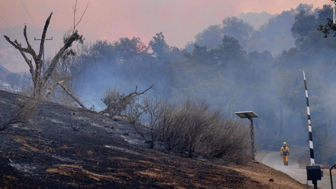 A firefighter walks down a road past a burnt hillside Saturday as the fire continues to burn in the foothills outside of Calabasas.