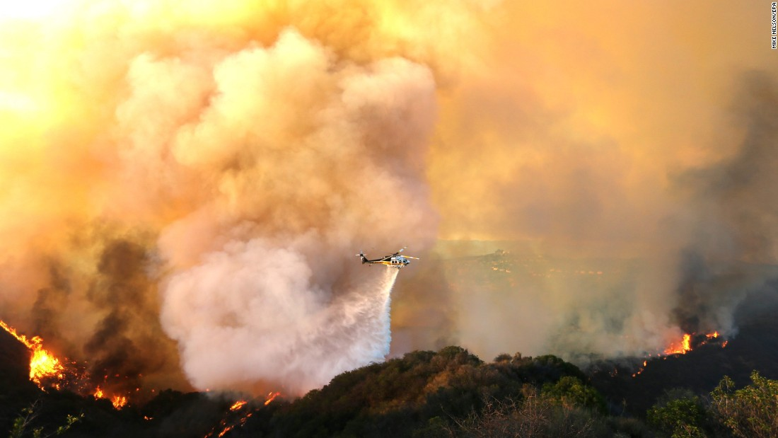 A helicopter drops water on the fire, which has forced the evacuation of at least 5,000 people, according to authorities.