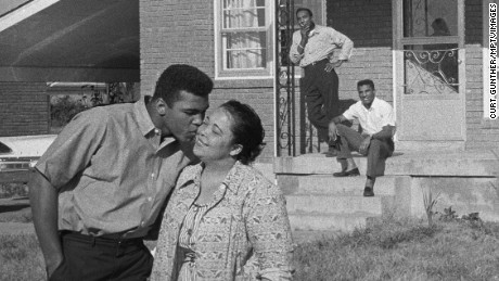 Cassius Clay kisses his mother, Odessa, in front of their Louisville, Kentucky home as his father, Cassius Sr., and brother, Rudy, look on