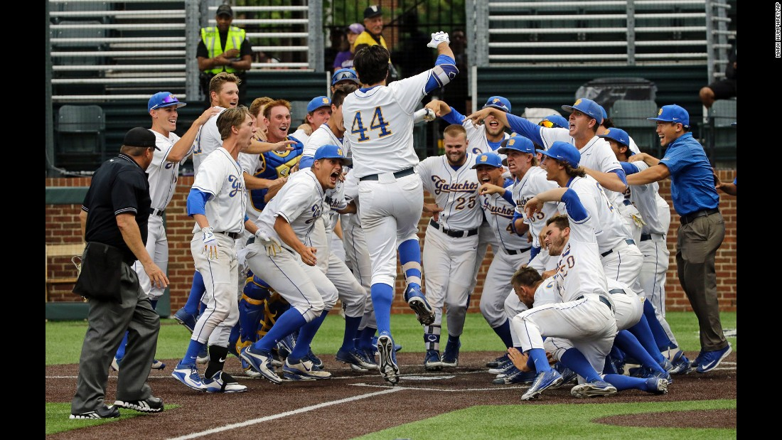 Austin Bush (No. 44) is welcomed at home plate by his UC Santa Barbara teammates after he hit a walkoff home run in the 14th inning to win an NCAA tournament game against Washington on Friday, June 3.