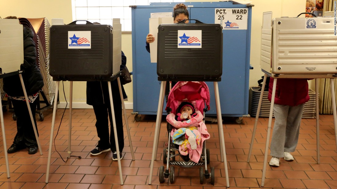 Adriana Reyes casts her vote as her 9-month-old daughter, Ariana, waits in Chicago on Tuesday, March 15.