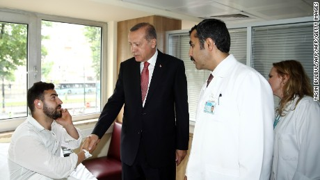 Turkish President Recep Tayyip Erdogan visits a man injured in the blast.