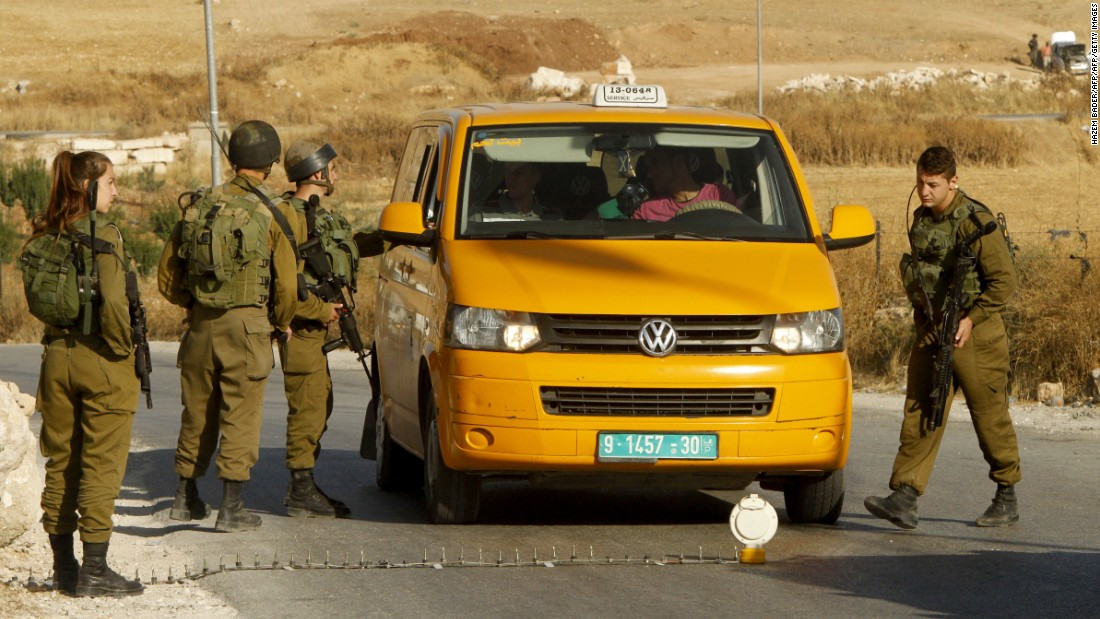 Israeli soldiers man a temporary checkpoint in the occupied West Bank on June 9, 2016. Israel said it had suspended entry permits for 83,000 Palestinians following a shooting in central Tel Aviv.
