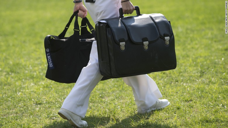 "A White House military aide and member of the US Navy carries a briefcase known as the ""football,"" containing emergency nuclear weapon codes, as US President Barack Obama departs on Marine One from the South Lawn of the White House in 2012."