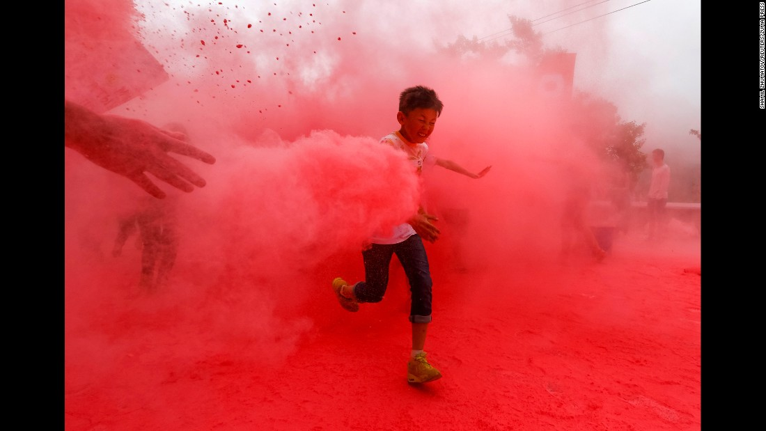 "Red powder is thrown on a participant during a ""color run"" race in Almaty, Kazakhstan, on Sunday, June 5."
