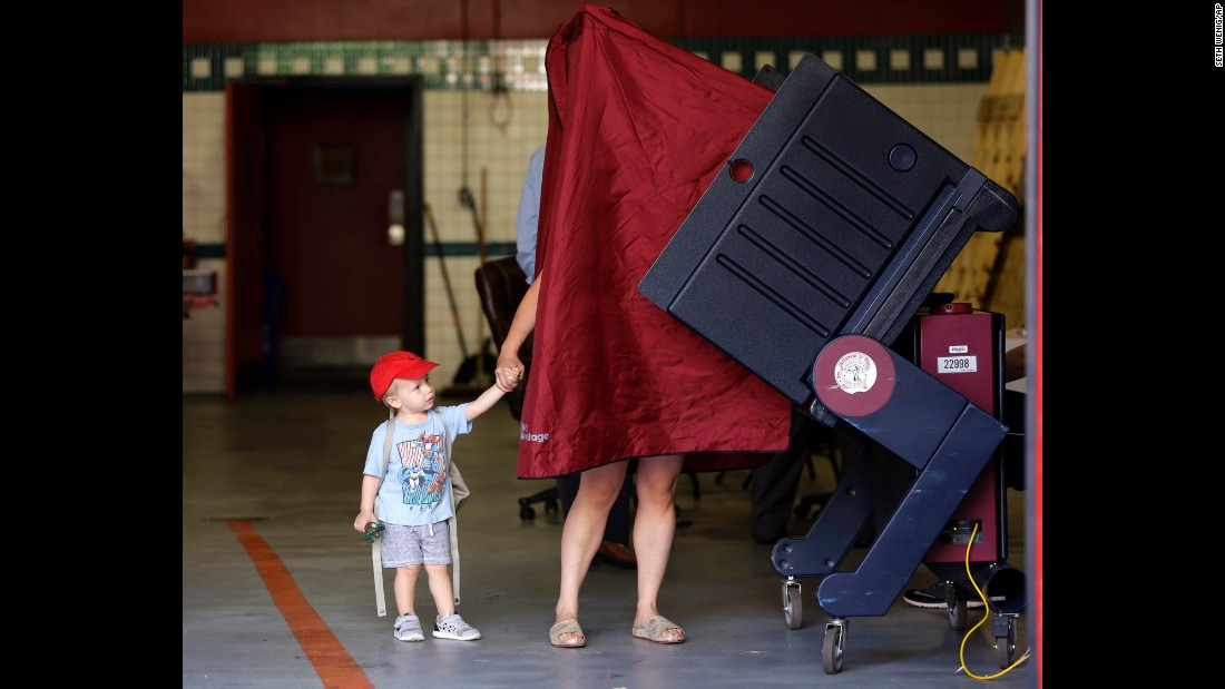 "James Percella, 2, holds his mother's hand as she steps into a voting booth in Hoboken, New Jersey, on Tuesday, June 7. <a href=""http://www.cnn.com/2016/06/07/politics/gallery/kids-voting-booths/index.html"" target=""_blank"">See more cute photos of children at the polls</a>"