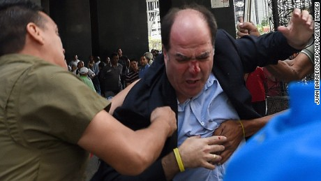 Supporters of Venezuelan president Nicolas Maduro hit opposition deputy Julio Borges(C), during a demonstration in front of the National Electoral Council in Caracas on June 9, 2016.  / AFP / JUAN BARRETO        (Photo credit should read JUAN BARRETO/AFP/Getty Images)