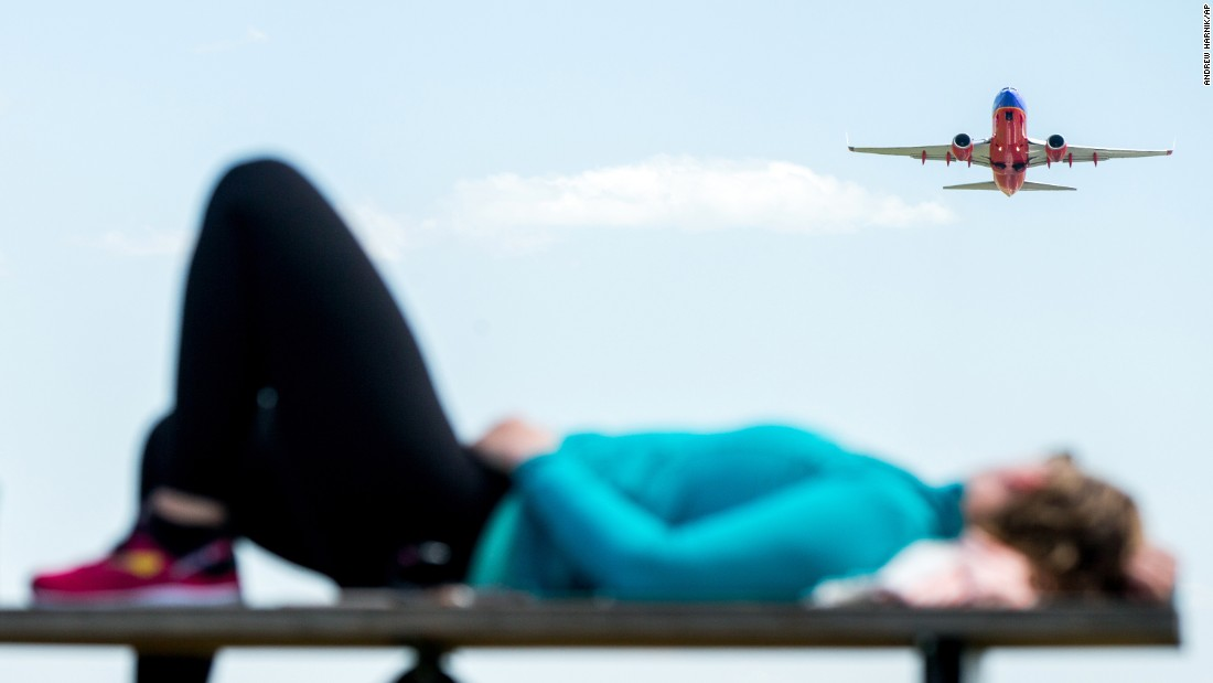 A plane takes off from Washington's Reagan National Airport as a woman relaxes on a picnic table in Arlington, Virginia, on Wednesday, June 8.