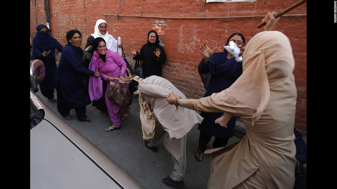 A police officer, right, tries to rescue her colleague from an angry worker of the Social Welfare Department during a scuffle in Srinagar, India, on Saturday, June 4. Employees of the Social Welfare Department had been protesting for job regularization and an increase in monthly wages.