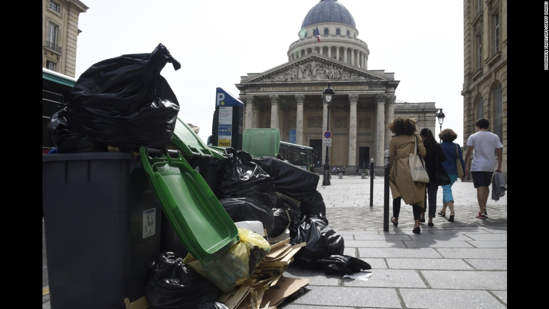 Pedestrians walk past rubbish bins on the pavement near the Panthéon in Paris on Friday, June 10. During nationwide strikes over labor reforms, garbage workers are refusing to pick up trash.