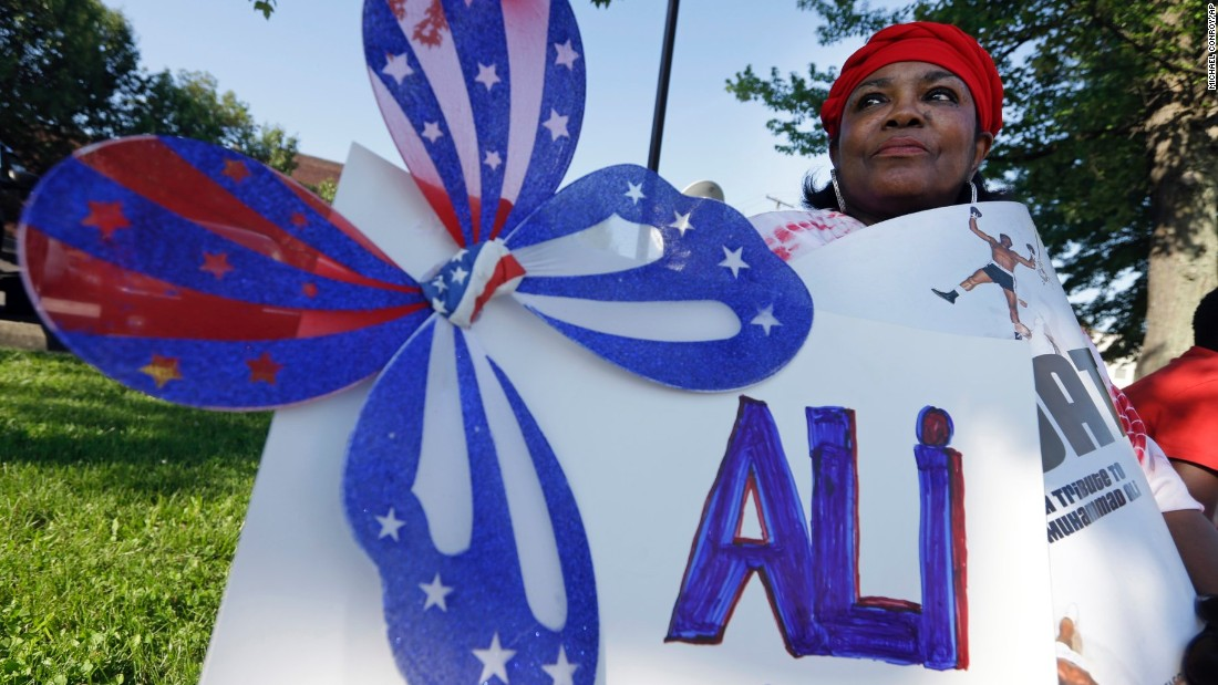 Frances Woods holds a sign saluting Ali as she awaits the procession.