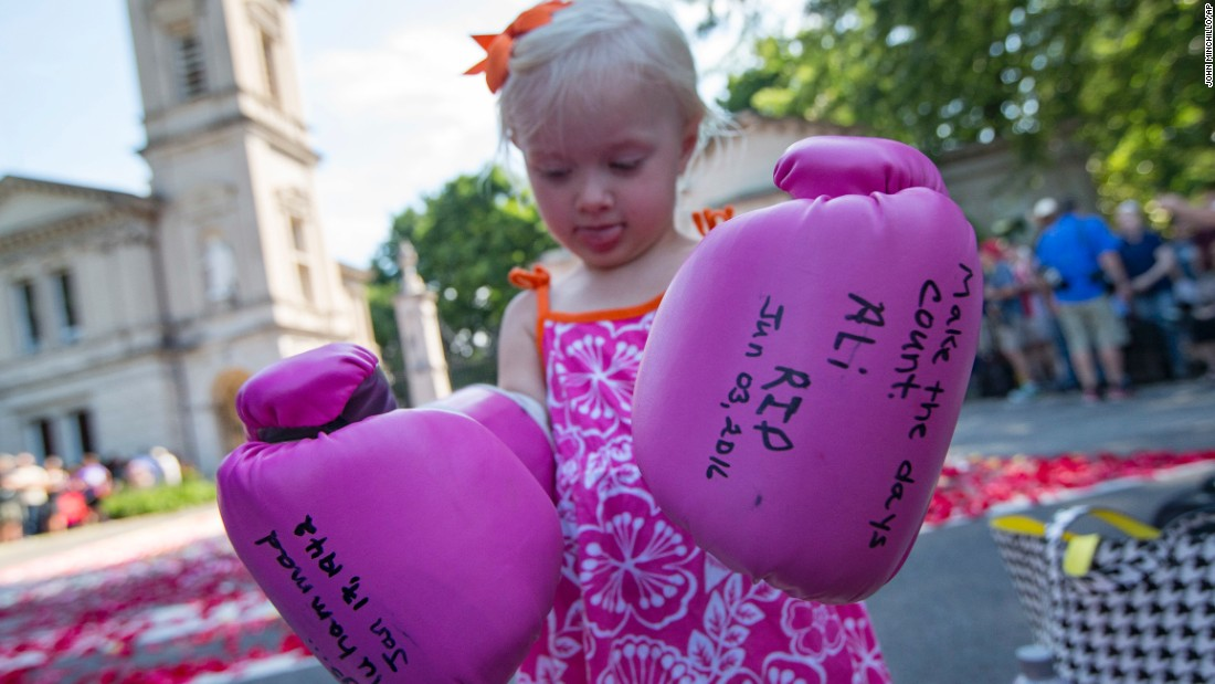 Lena Worthington, 2, wears oversized boxing gloves as spectators wait for the funeral procession.