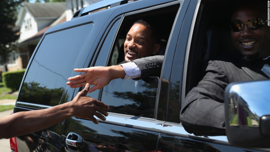 "Actor Will Smith greets the public while riding in the funeral procession. Smith played the boxer in the 2001 film ""Ali."""