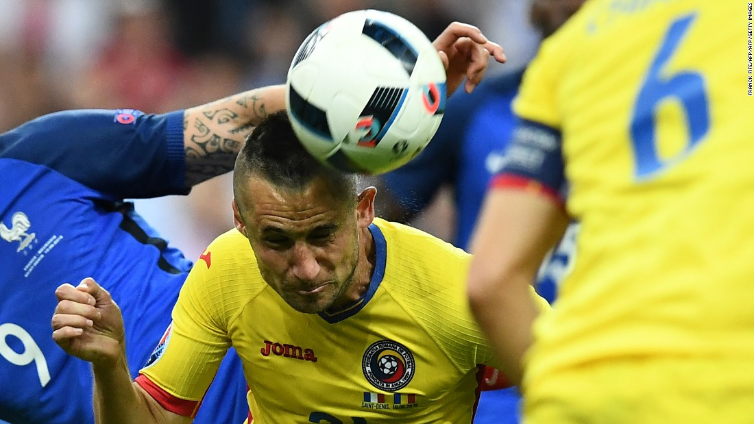 Romanian defender Dragos Grigore heads the ball during the match.