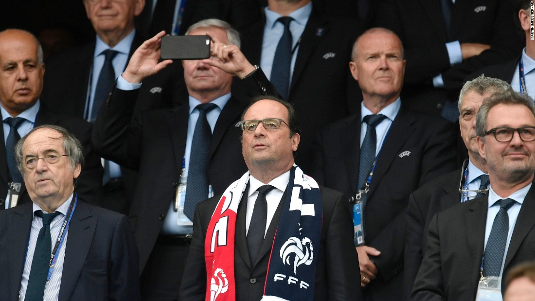 French President Francois Hollande wears a team scarf as he watches the opening ceremony from the stands.