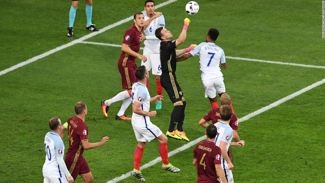 Russia goalkeeper Igor Akinfeev boxes the ball.