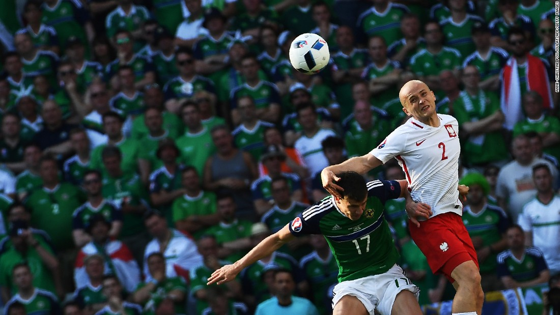 Northern Ireland's Paddy McNair, left, vies for the ball with Poland's Michal Pazdan.
