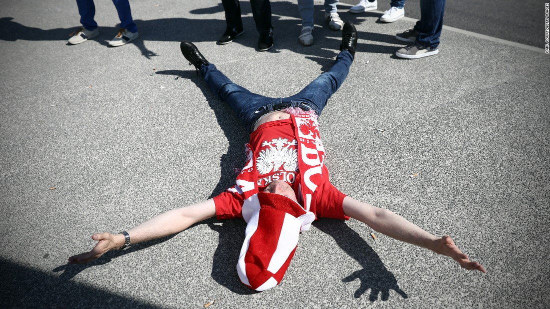 A Poland fan lies on the ground next to friends after they arrived to watch the game in Nice.