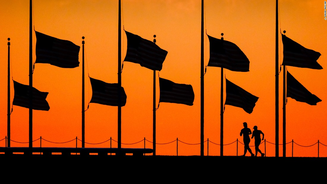 Runners pass under half-staff flags at the Washington Monument on June 13.