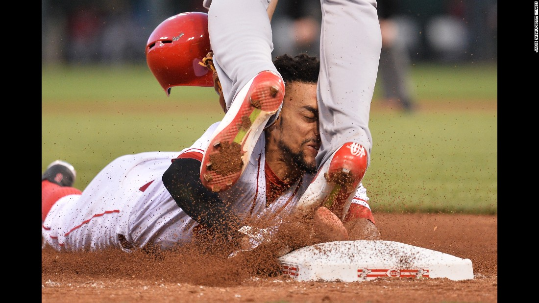 Cincinnati's Billy Hamilton slides into the legs of St. Louis' Jhonny Peralta while trying to steal third base on Wednesday, June 8.