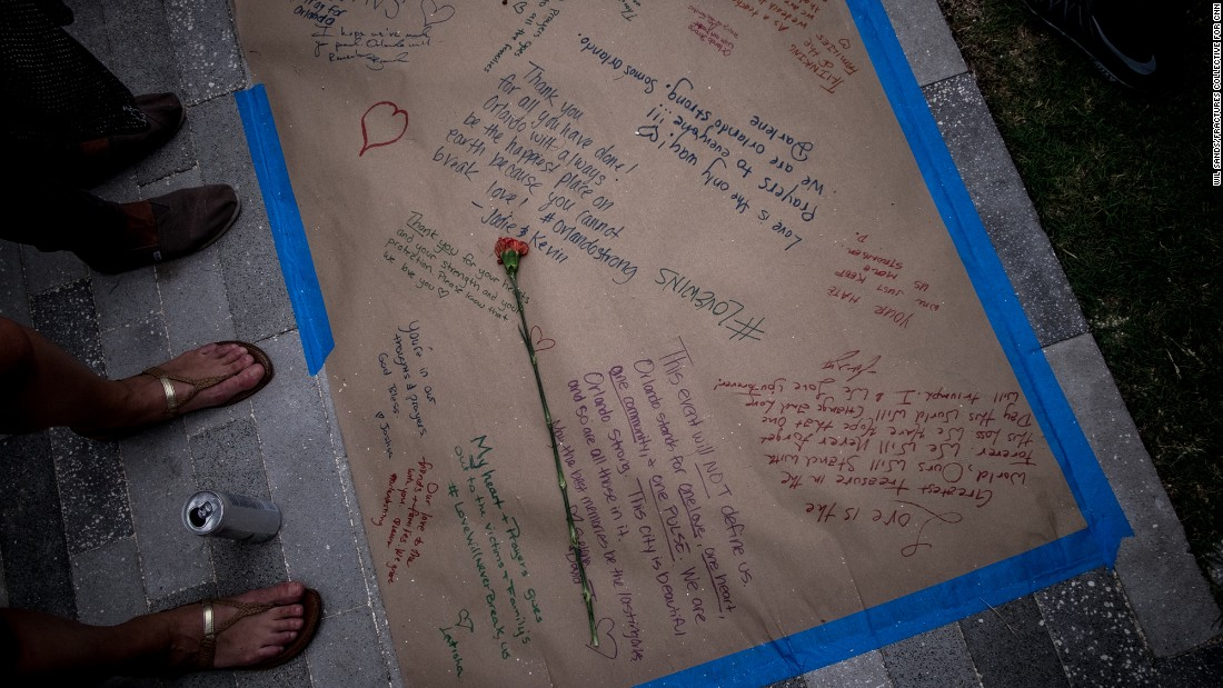 A flower is placed on a long sheet of paper adorned with heartfelt messages.