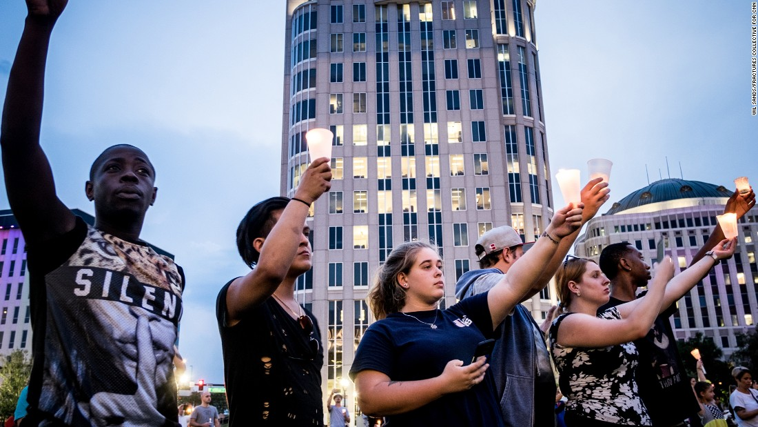 The crowd holds up candles during a moment of silence for the victims.