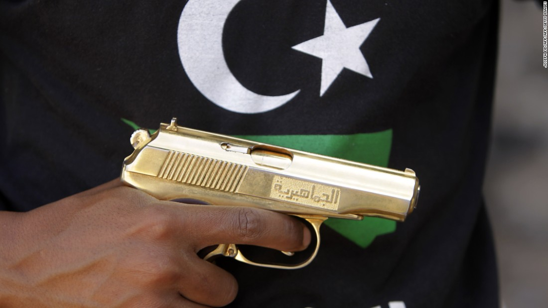 A Libyan fighter holds a golden gun found in the compound of Libya's ousted leader Moammar Gadhafi, in Bab al-Azizizyah, Tripoli, on September 25, 2011.