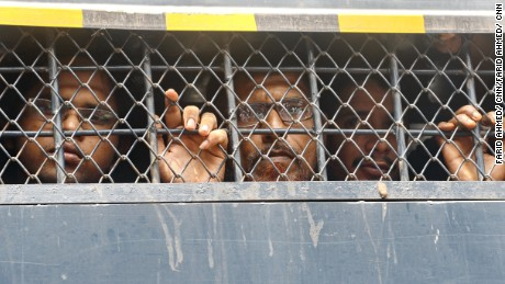 Detained Bangladeshis in a police van prison van as they are taken to the Dhaka Magistracy in Dhaka.