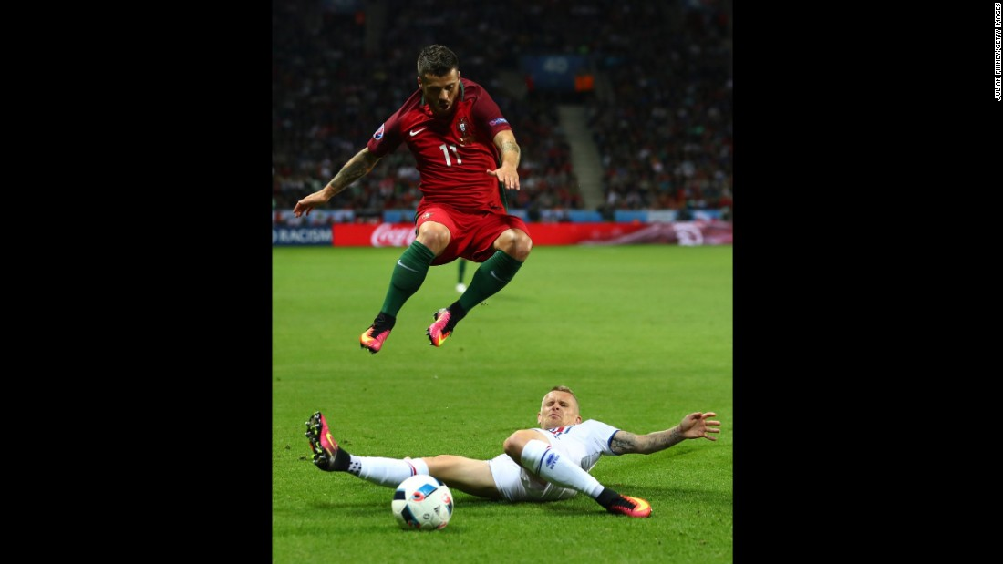 Vieirinha jumps over a tackle from Iceland's Ari Skulason.
