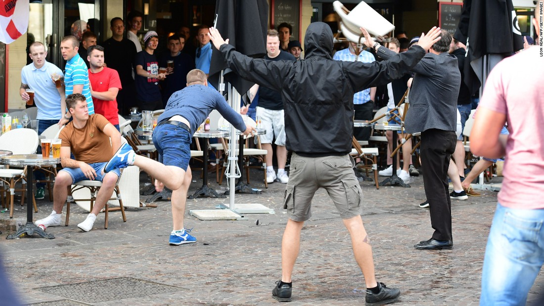A Russia fan lobs a chair towards England fans sitting in a cafe in Lille, France, on Tuesday. Many England fans going to Lens have to travel through nearby Lille, where Russia is playing Slovakia on Wednesday.