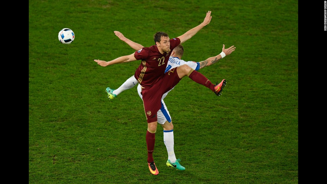 Slovakia's Jan Durica and Russia's Artem Dzyuba batlle for possession.