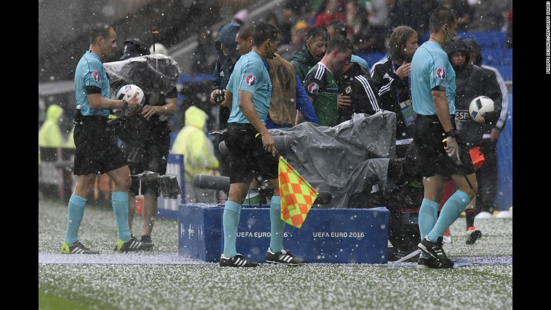 Referees leave the field after the match in Lyon, France, was temporarily stopped because of a hailstorm.