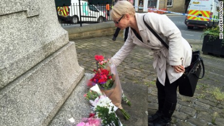 A mourner places flowers at Birstall's Market Square in honor of Jo Cox.