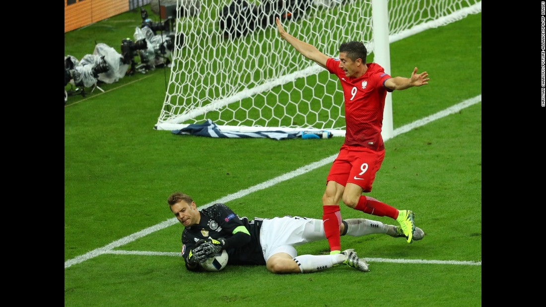German goalkeeper Manuel Neuer collects the ball near Poland's star forward, Robert Lewandowski.