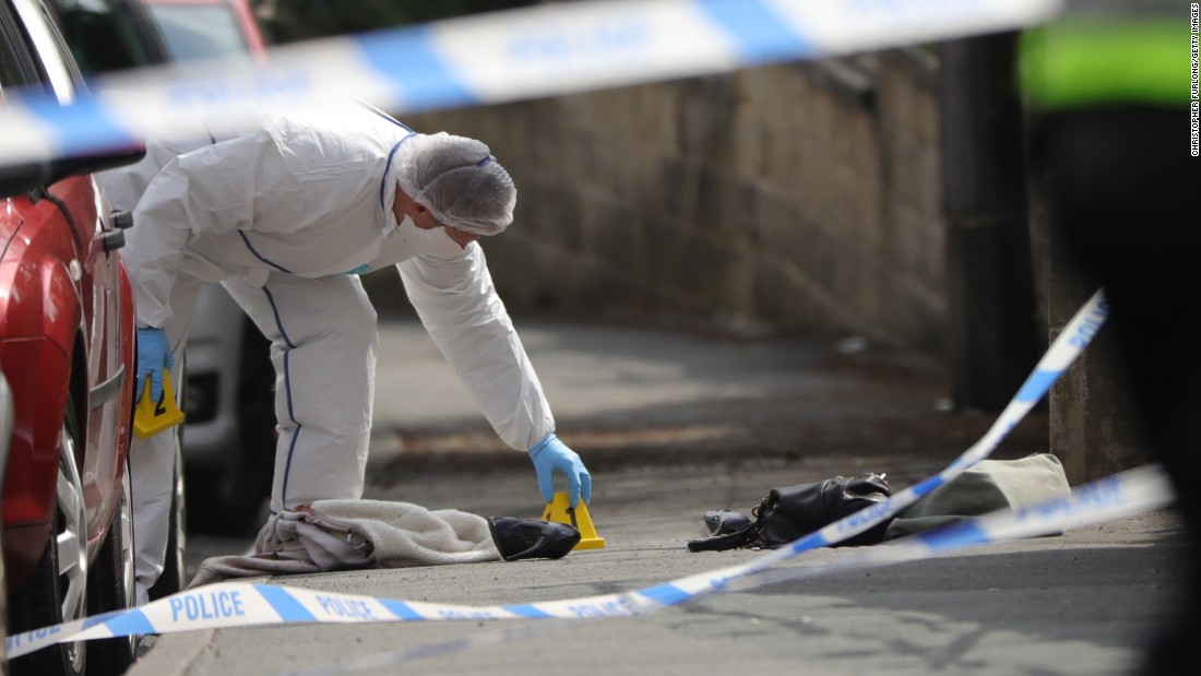 "A police officer examines shoes and a handbag at the scene where British politician Jo Cox <a href=""http://www.cnn.com/2016/06/16/europe/british-mp-jo-cox-attacked/index.html"" target=""_blank"">was attacked</a> in Birstall, England, on Thursday, June 16. The 41-year-old member of Parliament died as a result of her injuries, and police say they have arrested a 52-year-old man in connection with the attack."