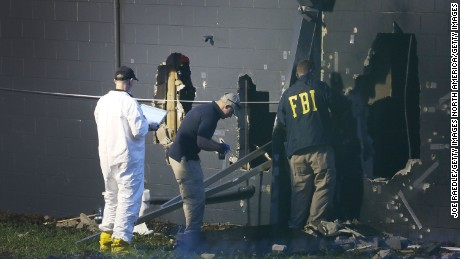FBI agents investigate near the damaged rear wall of the Pulse Nightclub.