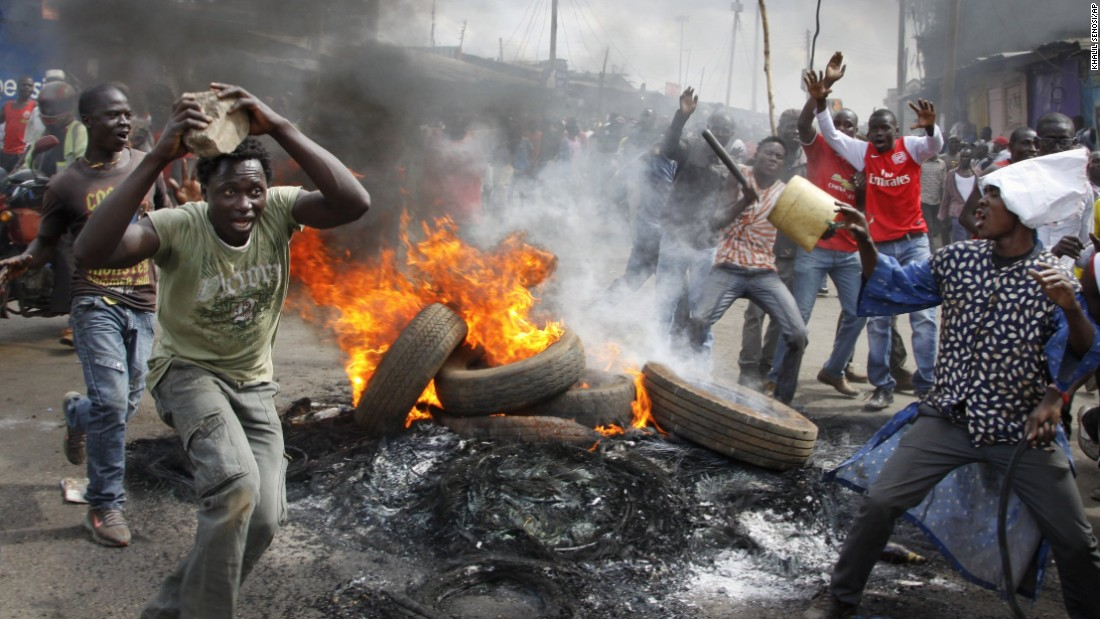 Opposition supporters stand by burning barricades as they protest in Nairobi, Kenya, on Tuesday, June 14.