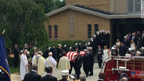 Lawrence Stack's wife Theresa follows the casket out of the church.