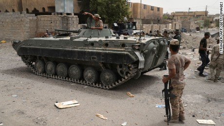 "Iraqi government forces patrol the centre of the city of Fallujah on June 18, 2016 as they hunt down holdout jihadists after retaking the Islamic State (IS) group's last remaining major hub in Iraq. While not fully under government control yet, Fallujah is the latest in a string of battlefield losses for IS, which has seen its two-year-old ""caliphate"" shrink significantly in recent months.   / AFP / STRINGER        (Photo credit should read STRINGER/AFP/Getty Images)"