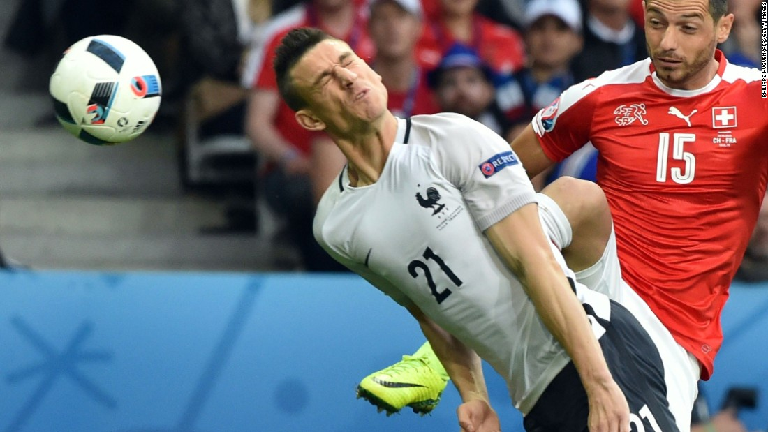France's defender Laurent Koscielny heads the ball next to Switzerland's midfielder Blerim Dzemaili .