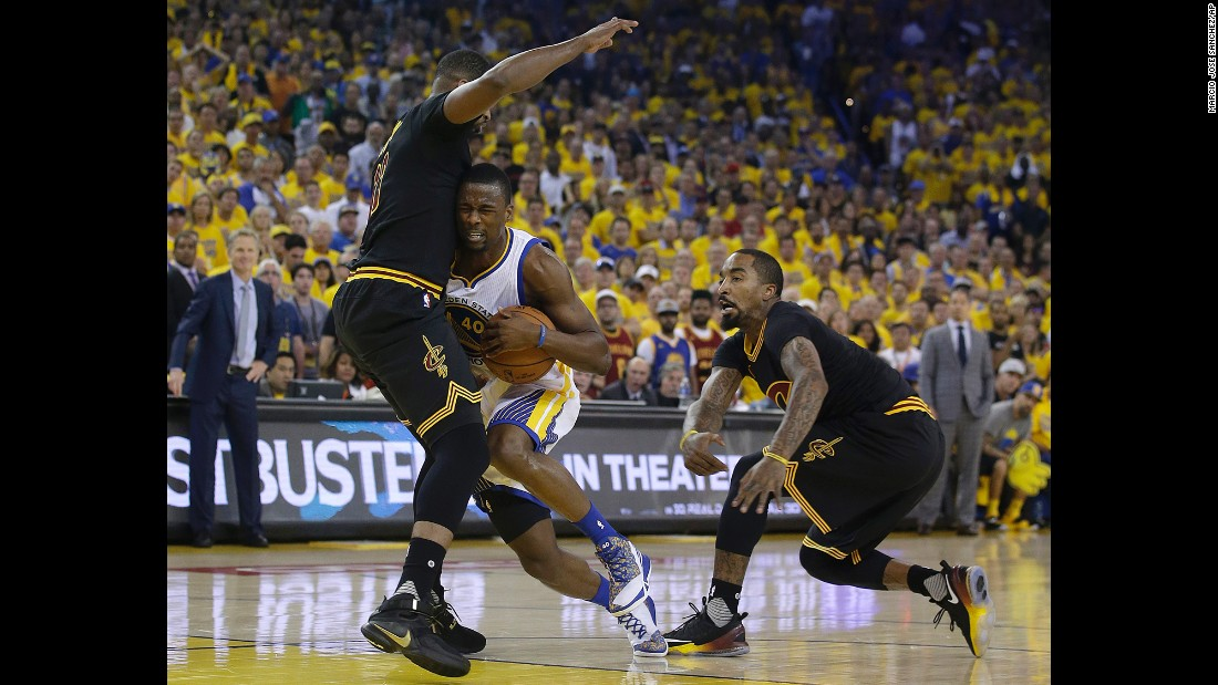 Warriors forward Harrison Barnes tries to drive past Cavaliers center Tristan Thompson, left, and guard J.R. Smith.