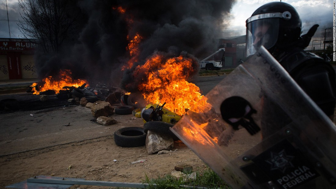 "An officer walks past burning debris during <a href=""http://www.cnn.com/2016/06/20/americas/oaxaca-mexico-clashes/index.html"">deadly clashes between striking teachers and police</a> in Oaxaca, Mexico, on Sunday, June 19. The violence came after seven days of protests disrupting traffic on a major highway connecting Oaxaca to Mexico City, the government said."