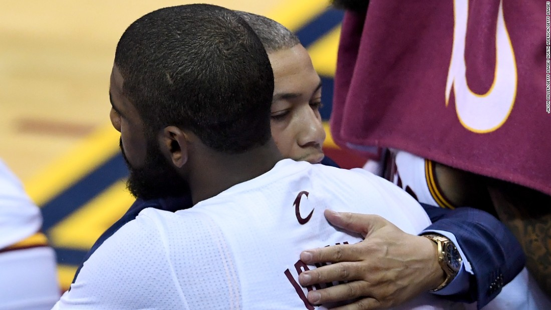Head coach Tyronn Lue (in suit) hugs Kyrie Irving of the Cleveland Cavaliers in post-game celebration. Lue broke down in tears on the Cavaliers bench immediately after the game.